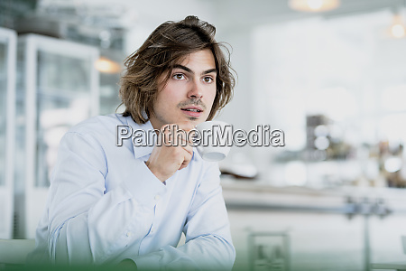 thoughtful male professional drinking coffee while