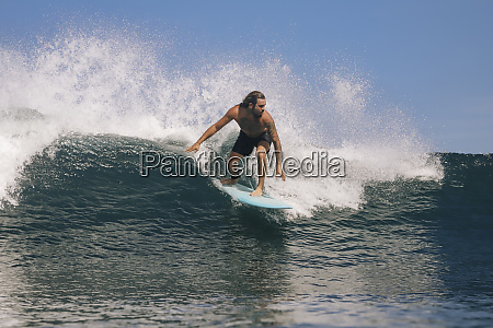 shirtless man surfing on sea against