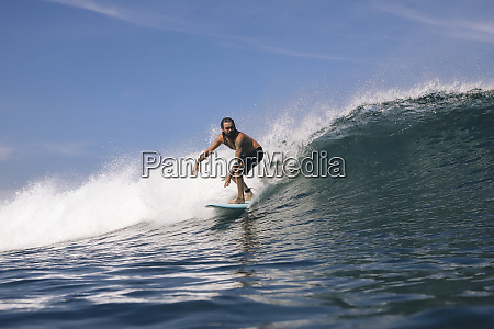 shirtless mid adult man surfing on