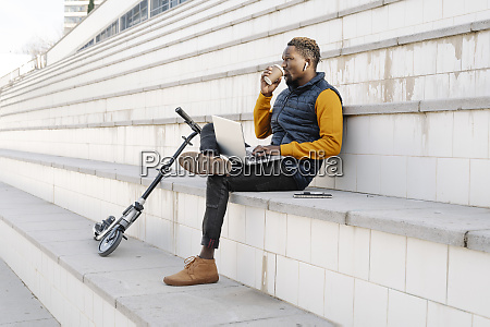 young man with laptop and scooter