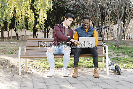 two young men sitting on park