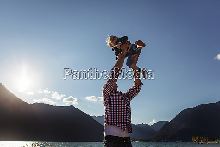 father holding aloft daughter against blue