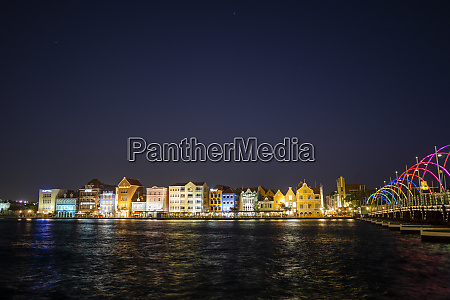 illuminated buildings by sea against clear