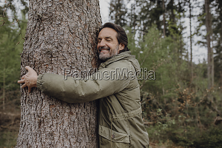 mature hiker hugging tree trunk