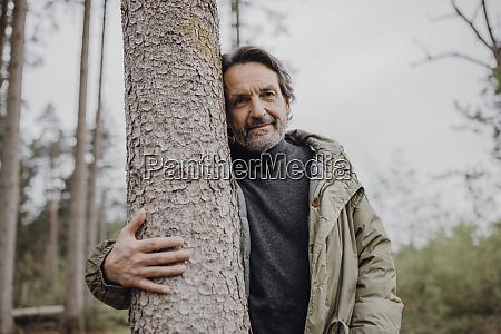 mature hiker hugging tree trunk
