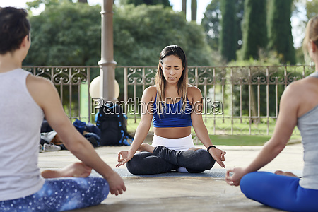 yoga instructor practicing lotus position with