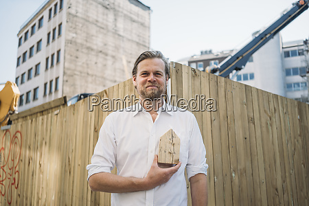 businessman holding wooden house model at