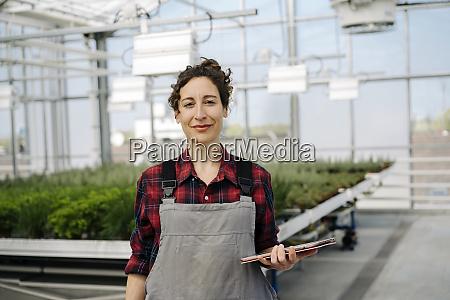 portrait of confident woman holding tablet