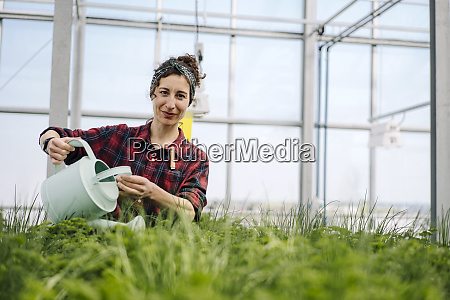 woman watering plants in greenhouse of