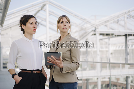 two businesswomen with tablet having a