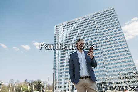 businessman using smartphone in the city
