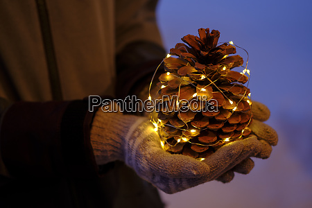 illuminated pine cone held by teenage