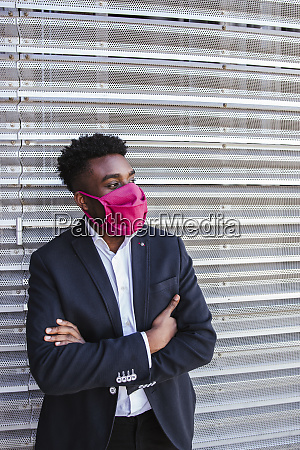 thoughtful businessman wearing mask with arms