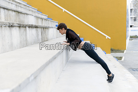 athletic woman exercising plank on stairs