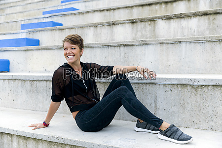 athletic woman sitting on stairs