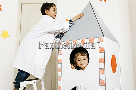 siblings playing astronaut and researcher at