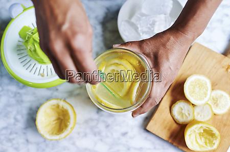 hands of womanstirringfresh lemonade