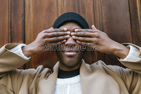 young woman covering eyes with hands