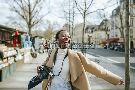 cheerful woman holding dslr camera on