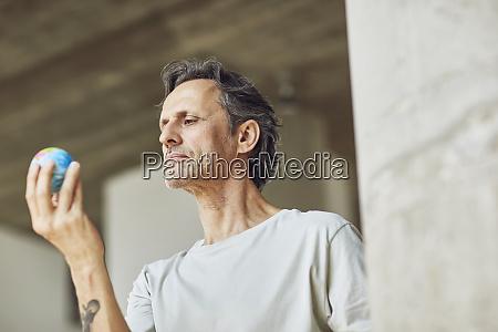 senior man holding mini globe in
