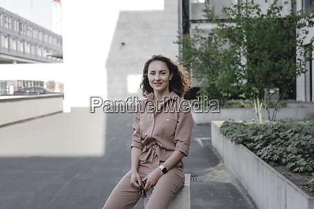 confident businesswoman sitting outside office building