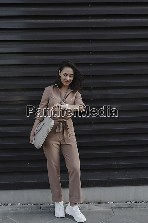 businesswoman checking smart watch while standing