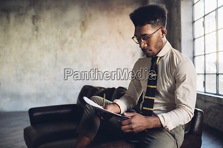 creative businessman taking notes on armchair