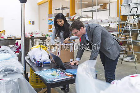 businessman using laptop and female employee