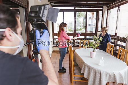 man filming reporter interviewing senior woman