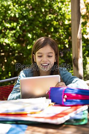 girl sitting at garden table doing