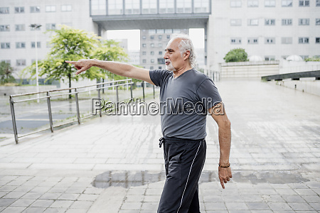 senior man pointing while standing on