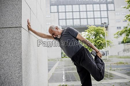 senior man stretching leg while standing