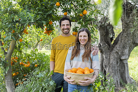 smiling couple with oranges standing against