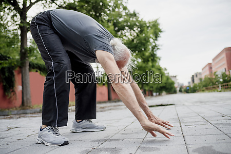 active senior man with arms raised