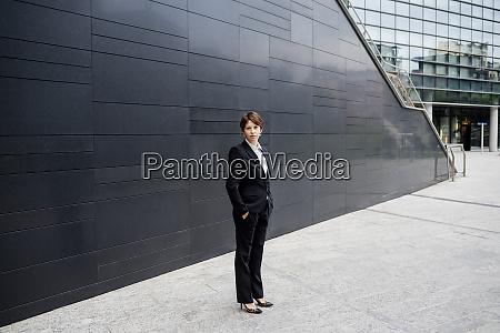 confident businesswoman standing on sidewalk against