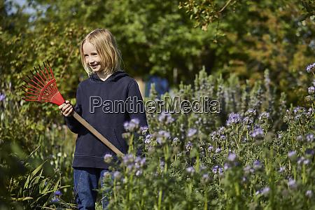 smiling girl in allotment garden holding