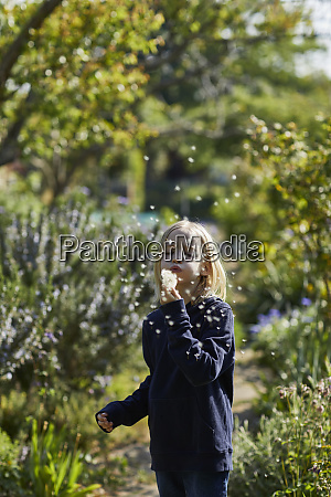 girl in allotment garden blowing a