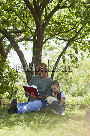 relaxed grandfather and granddaughter in garden