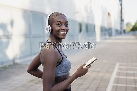 smiling young woman wearing headphones using