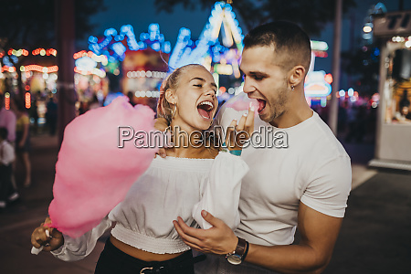 cheerful young woman feeding cotton candy