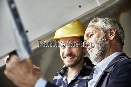 architect and worker measuring window on