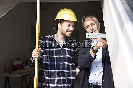 smiling construction worker looking at measurement