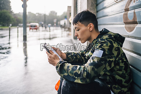 man using digital tablet against shutter