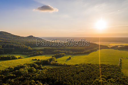 sun shining over forested hills of