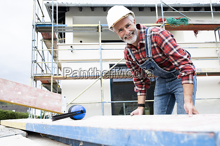 smiling male architect carrying wood while
