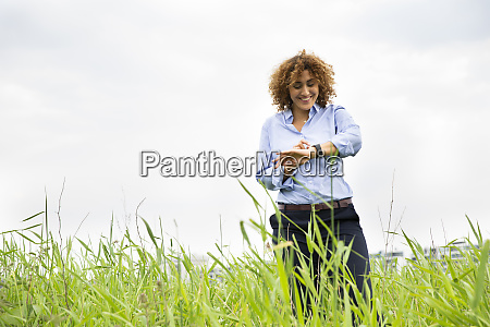 smiling businesswoman checking time while standing