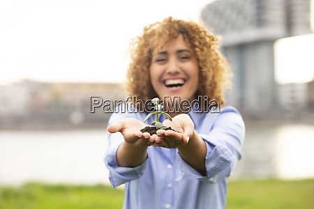 cheerful businesswoman with curly hair holding