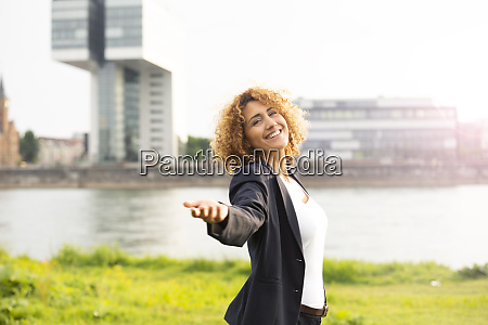 smiling businesswoman with arm outstretched standing