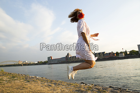 mid adult woman wearing mask jumping