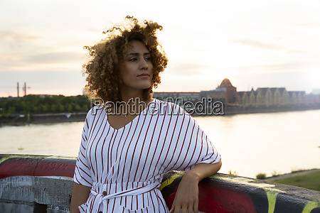 thoughtful woman with curly hair standing